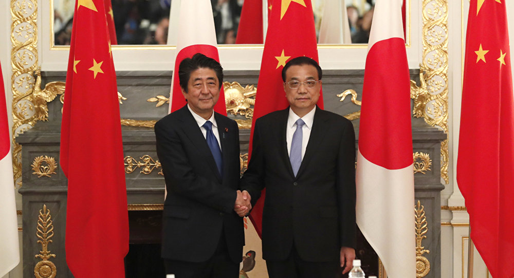 China's Premier Li Keqiang (R) shakes hands with Japan's Prime Minister Shinzo Abe (L) at the start of their bilateral talks