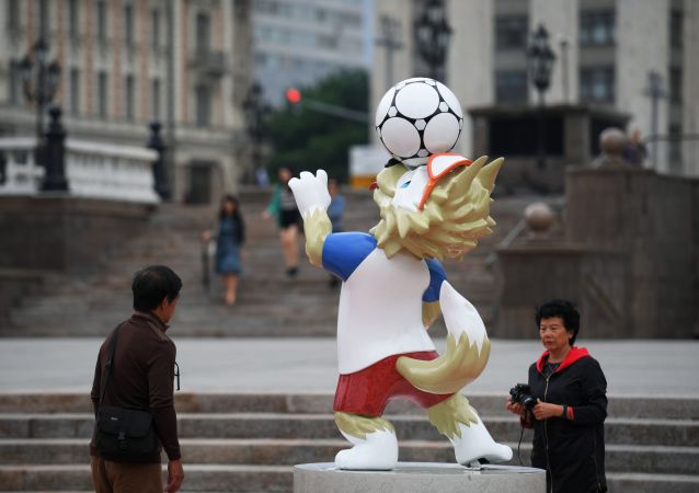 Туристы у фигуры официального талисмана чемпионата мира по футболу 2018 волка Забиваки, установленной к чемпионату мира по футболу 2018, на Манежной площади в Москве