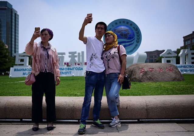A group of people use their mobile phone to take pictures in front of a sign of Shanghai Cooperation Organisation (SCO) in Qingdao