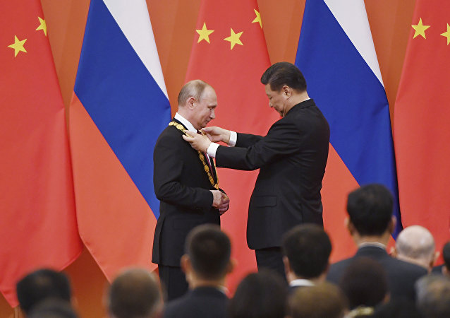 Chinese President Xi Jinping, right, presents the Friendship Medal to Russian President Vladimir Putin in the Great Hall of the People in Beijing