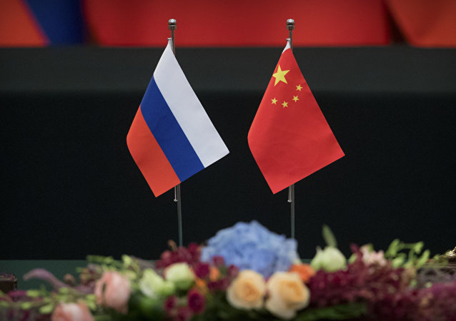 Russian, left, and Chinese flags sit on a table before a signing ceremony at the Great Hall of the People in Beijing