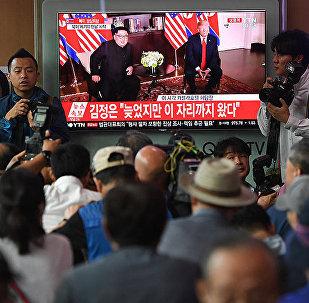Люди смотрят вст речу Ким Чен Ына и Трампа