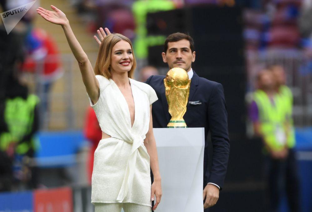 2018世界杯开幕式前夕,俄罗斯超模纳塔利娅·沃佳诺娃和西班牙球星伊克尔·卡西利亚斯携大力神杯亮相卢日尼基体育场。