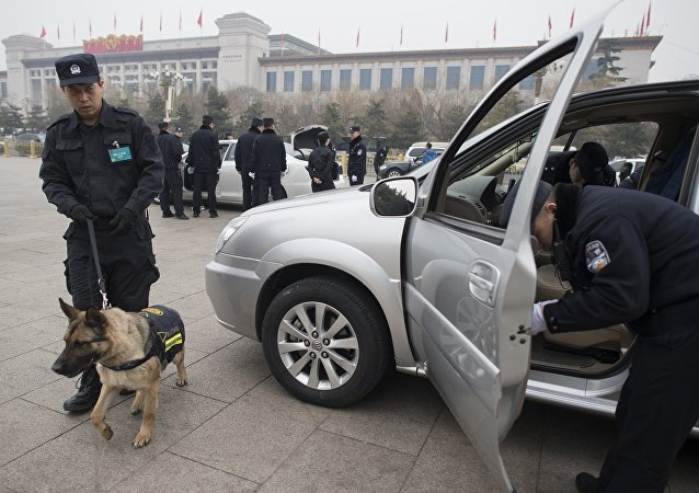 Chinese police officers search vehicules at a security check point outside the Great Hall of the People