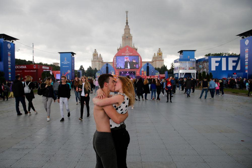 以麻雀山上的莫斯科大学旁的国际足联球迷节开幕式为背景接吻的情侣。