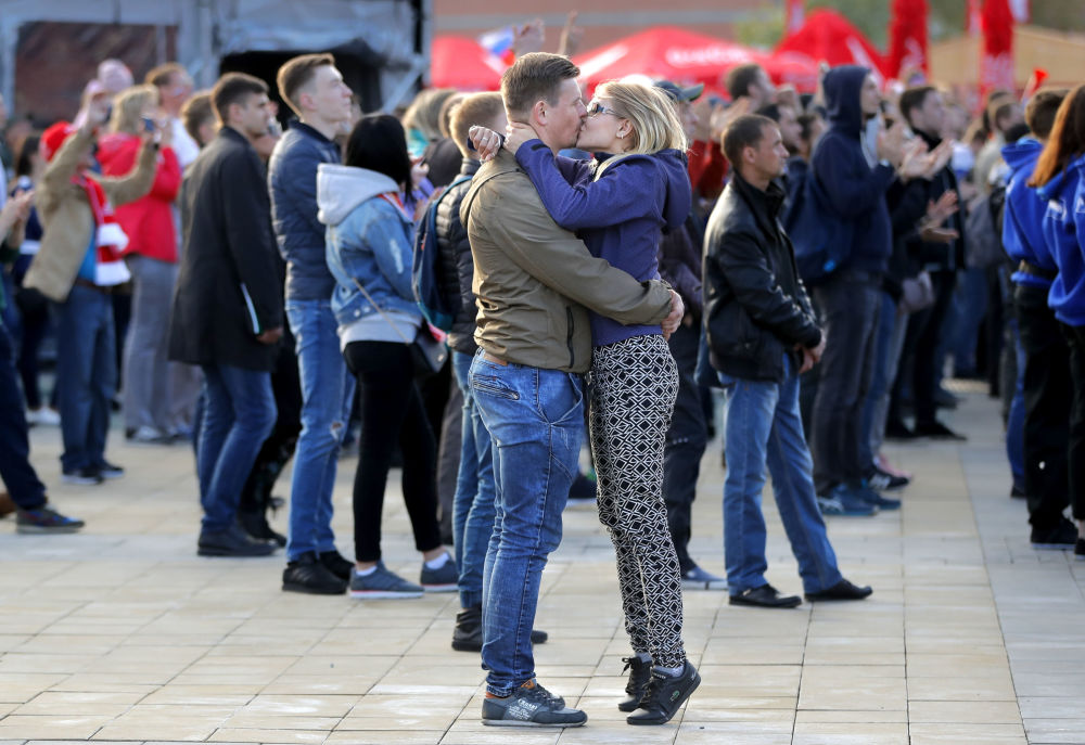 以在叶卡捷琳堡的俄罗斯和沙特阿拉伯比赛为背景接吻的球迷。
