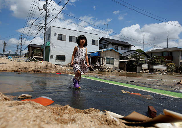 A local resident walks in a flood affected area in Mabi town in Kurashiki