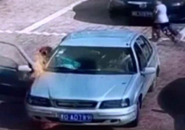 一中国男子试图吹灭一辆燃烧的轿车