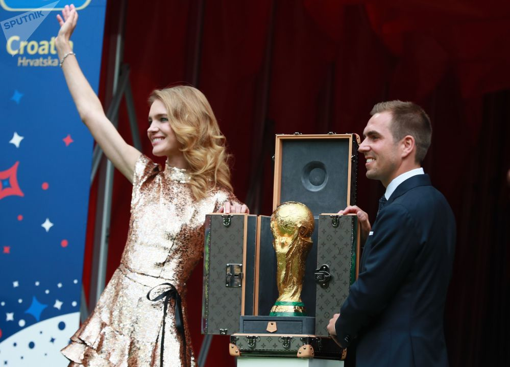 """""""赤子之心""""基金会创始人娜达莉亚•沃佳诺娃和足球运动员菲利普•拉姆将奖杯带到世界杯赛闭幕式上。"""
