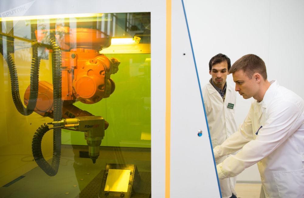 國立核能研究大學-莫斯科工程物理學院激光和等離子技術研究所代主任安德烈·庫茲涅措夫認為,在不久的將來,激光科學的發展將能夠創造出在宇宙整個生命週期內滯後一微秒並非常明確地對萬有引力變化做出反應的時鐘,還可以控制熱核子能。 圖片說明:激光和等離子技術研究所的研究生安裝調試帶有機械手和400瓦特摻鐿光纖激光器的裝置。