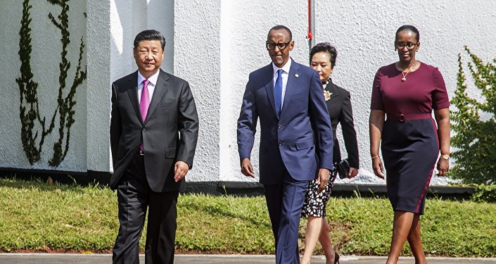 Rwandan President Paul Kagame, right, and Chinese President Xi Jinping, followed by their wives Jannette Kagame and Peng Liyuan arrive at Rwanda's State House