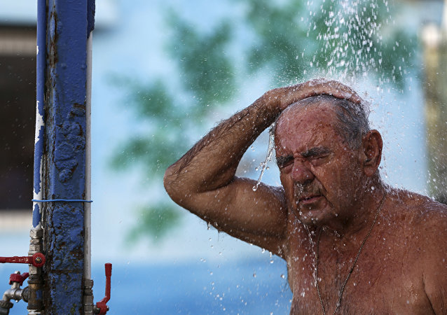 A man takes a shower at a beach of Alimos suburb in Athens, on Saturday, July 1, 2017. A summer heatwave has hit Greece, with temperatures reaching a high of 43 degrees Celsius (111 Fahrenheit) in Athens, and is expected to last over the weekend.
