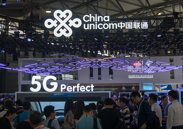 People visit a China Unicom stand displaying 5G technology during the Mobile World Conference in Shanghai