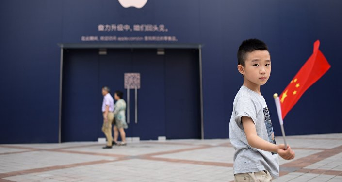 A boy holds a Chinese flag as he walks past an Apple Store undergoing renovation in Beijing