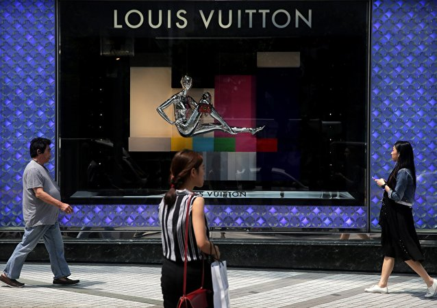 Pedestrians walk past a high end fashion store