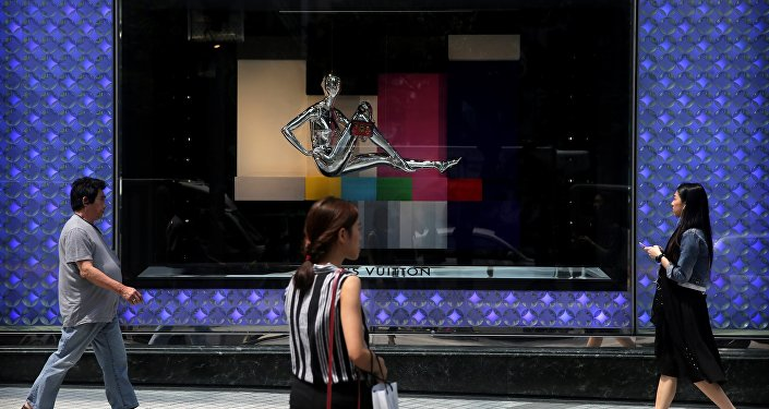 Pedestrians walk past a high end fashion store