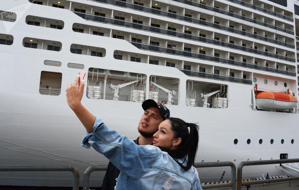 人們以停靠在符拉迪沃斯托克海運碼頭的地中海輝煌號郵輪為背景拍照留念。
