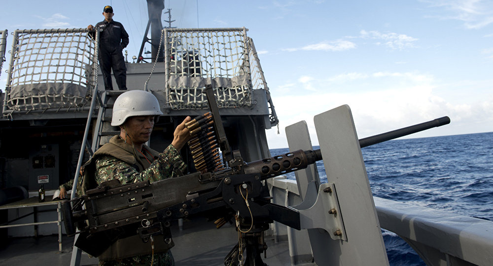 A Philippine Navy personnel loads bullets for a .50 caliber machine gun