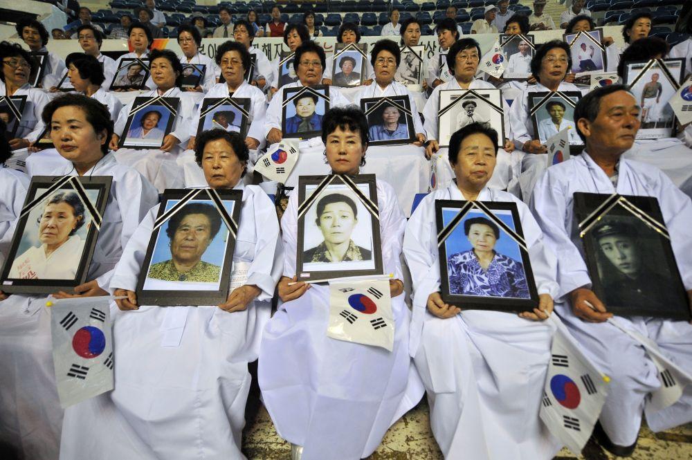 朝鮮人手捧在紀念從日本殖民統治下解放66週年的反日遊行中死去的家庭成員肖像。