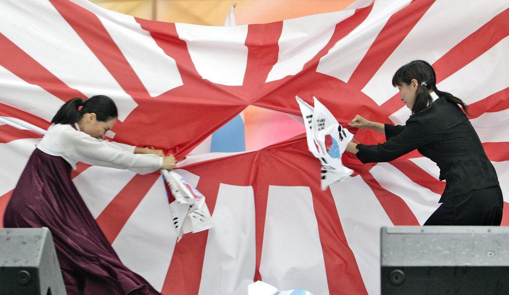 韓國大學生們在韓國半島從日本殖民統治下解放週年紀念日的紀念遊行中撕毀日本殖民統治時的日本國旗。