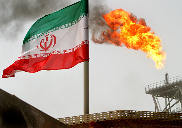 A gas flare on an oil production platform is seen alongside an Iranian flag