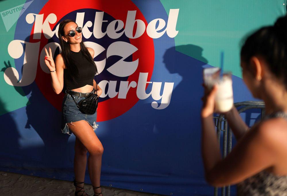 一名女孩在2018 Koktebel爵士音樂節的橫幅式廣告旁拍照。