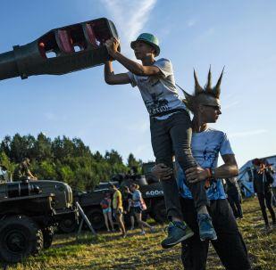 """观众在特维尔州大扎维多沃村军事武器展的""""入侵""""露天音乐节上。"""