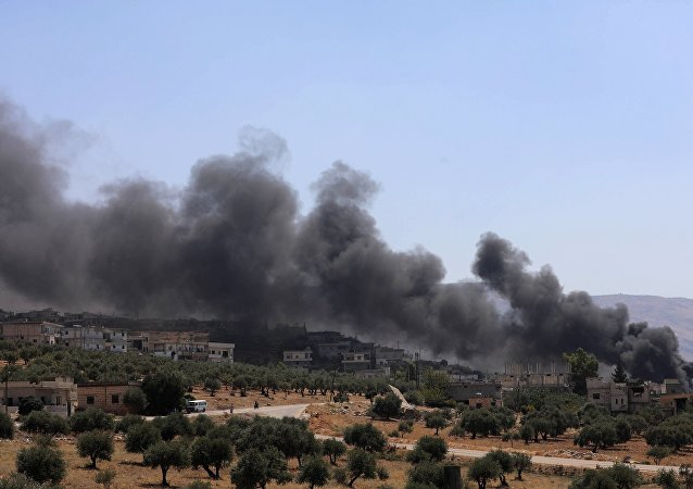 Smoke blowing from buildings on fire that were hit by reported Russian air strikes in the rebel-held town of Muhambal, about 30 kilometres southwest of the city of Idlib