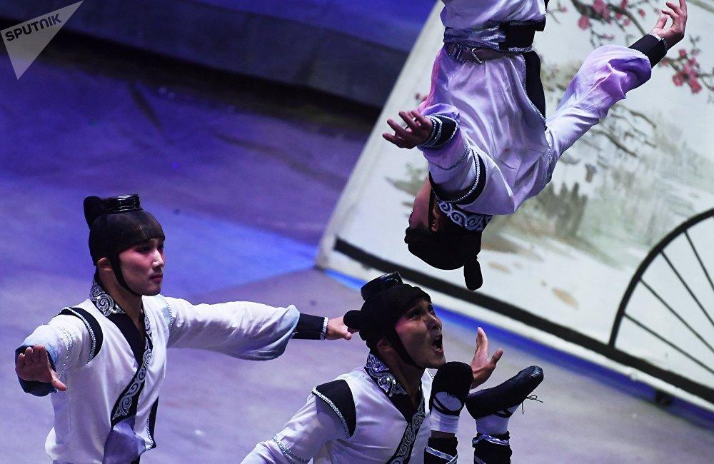 中國馬戲演員在頭頂表演的具有高潮平衡技巧的扇子舞