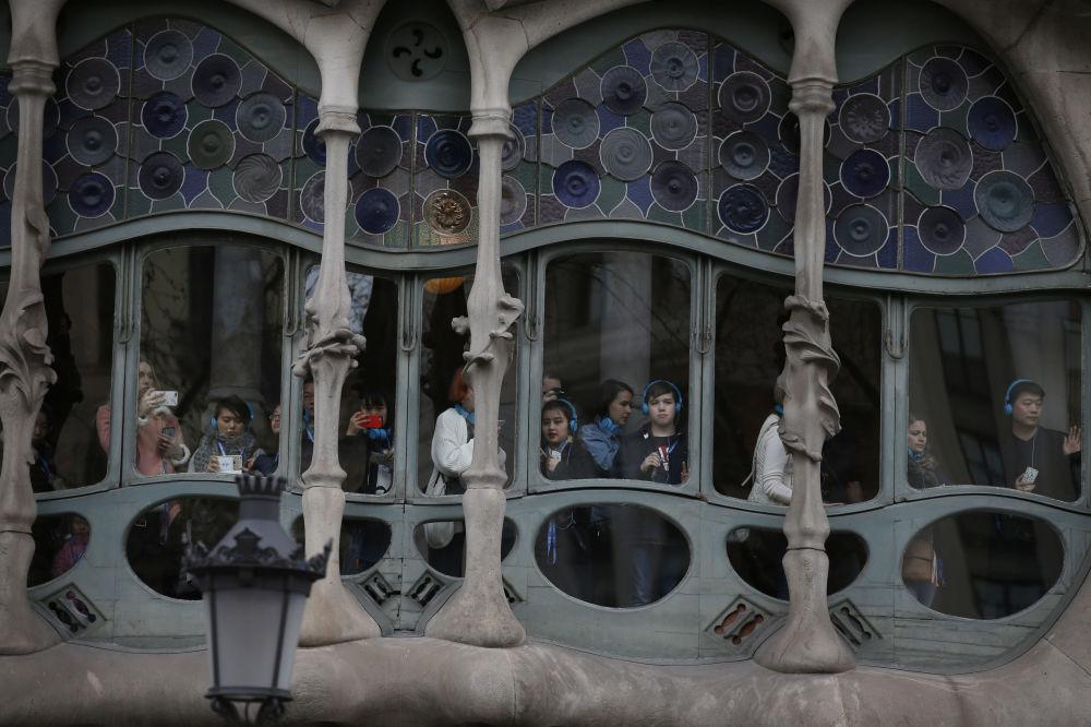 西班牙巴塞罗那,游客从建筑师安东尼·高迪设计的巴特罗公寓的窗户向外眺望