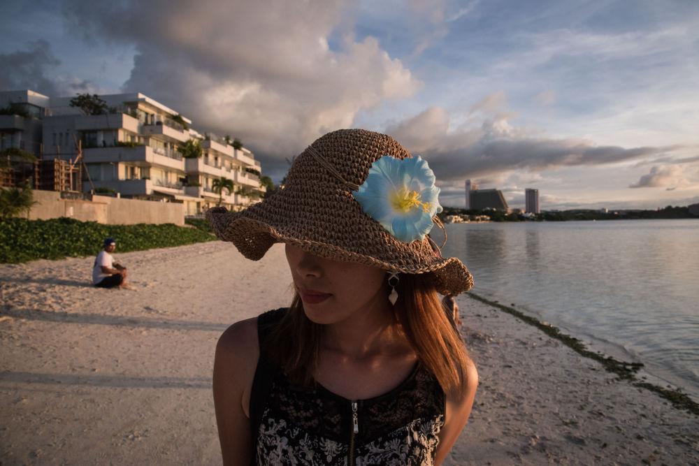 游客在美国关岛杜梦湾海岸边