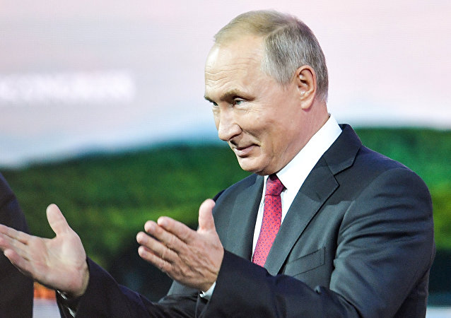 Russian President Vladimir Putin greets the audience as he attends a session of the Eastern Economic Forum in Vladivostok