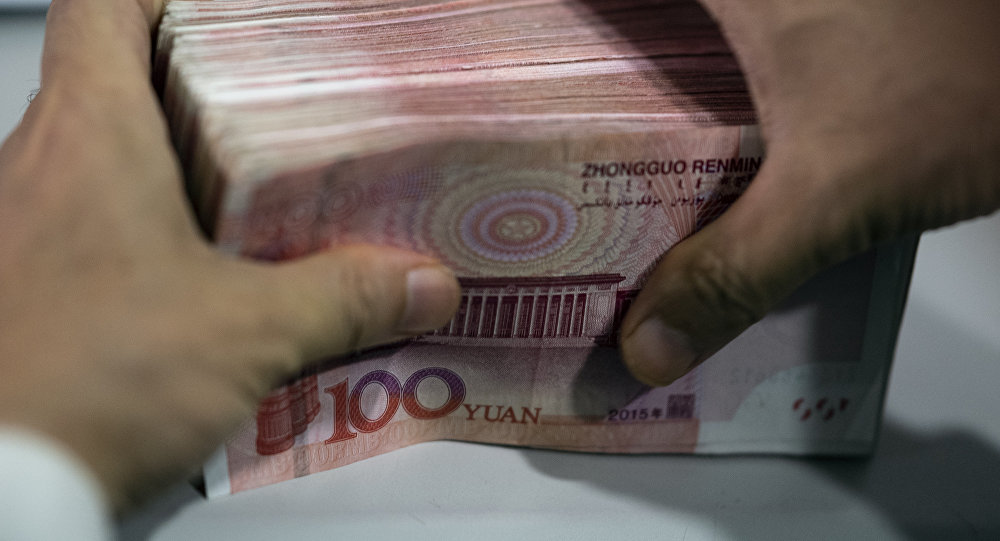 A bank employee counts out 100 yuan notes at a bank in Shanghai