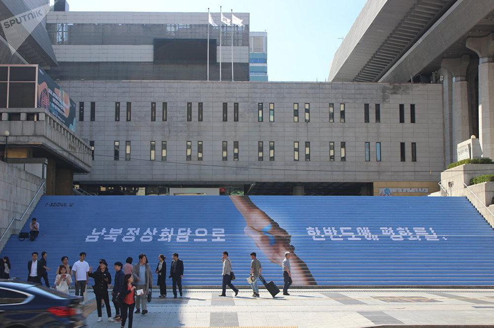 世宗文化中心的主要楼梯梯饰装饰着握手的图案和朝鲜半岛的轮廓,上面写着: 通过朝韩首脑会晤走向半岛和平