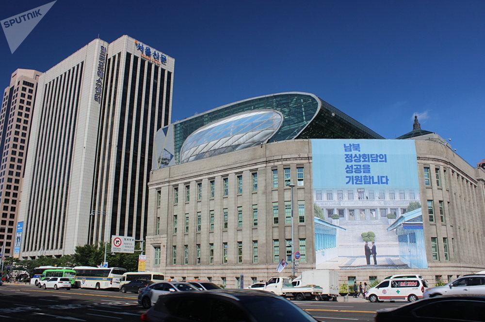 首尔市政府大楼前,文在寅和金正恩历史性握手的图案和上面写着: 期待韩朝首脑会晤取得圆满成功!