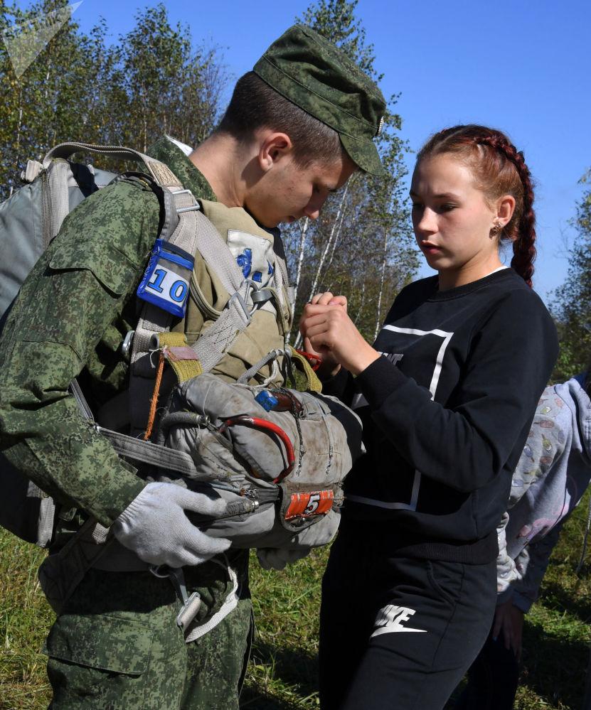一名来自阿尔谢尼耶夫市航空俱乐部的女孩在滨海边疆区诺沃瑟索耶夫克村附近的野战机场跳伞前帮助乌苏里斯克苏沃洛夫军事学校的学员穿上降落伞