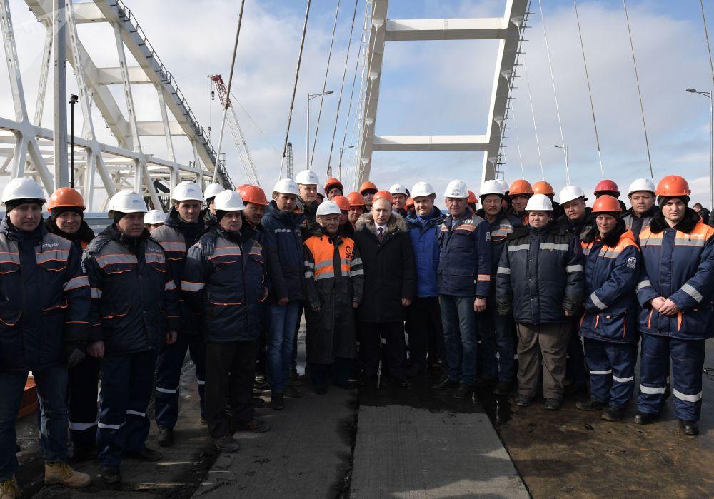 俄罗斯总统弗拉基米尔·普京和施工人员查验穿越克里米亚海峡的克里米亚大桥公路的完工部分