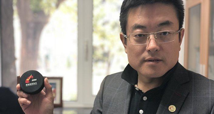 中国冰球协会常务副秘书长徐成响拿着习近平和普京打过的冰球