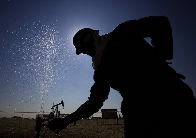 Нефтяник корректирует клапан, выпускающий распыление воды при работе на нефтепроводах на пустынных нефтяных месторождениях