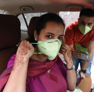 """印度""""Red FM """"电台的主持人戴着防护面具,新德里,印度"""