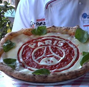 用番茄酱绘制足球运动员肖像的披萨