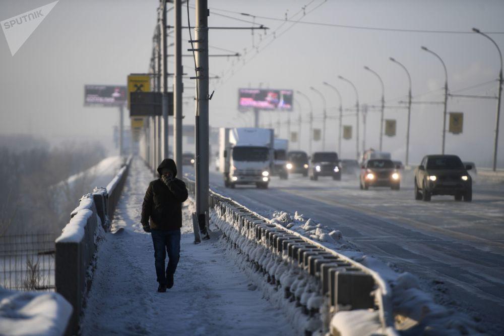 一名男子步行在新西伯利亞市橫跨鄂畢河的德米特羅夫斯克橋上