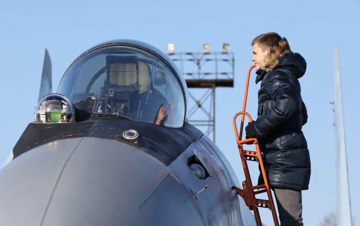 """年轻男子检查""""俄罗斯猎鹰""""飞行表演队苏-35S战斗机驾驶舱"""