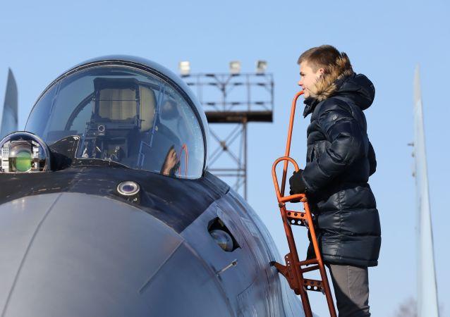 年輕男子檢查「俄羅斯獵鷹」飛行表演隊蘇-35S戰鬥機駕駛艙