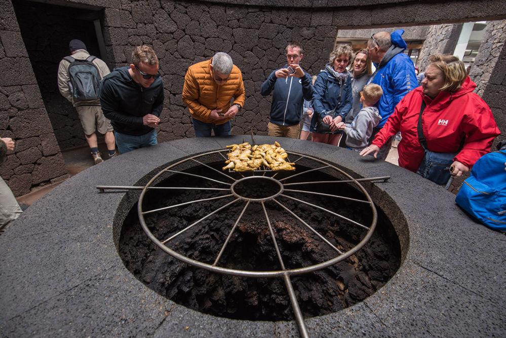 """西班牙兰萨罗特岛上的""""魔鬼""""餐厅 (El Diablo)。建造""""魔鬼""""餐厅的想法属于一位雕塑家,他与自己的建筑师朋友共同设计了火山口上的巨大烤箱。餐厅提供肉类和海鲜,但它的吸引力不止如此。大厅的设计也很有趣,是一个封闭式的圆形观景台,可以饱览火山全景,让人有种身在火星的错觉。"""