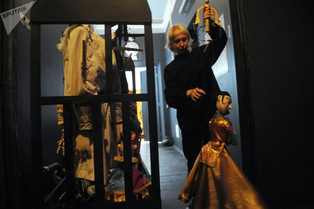 """在下层木偶剧院(木偶剧)中,借助于线、杆或金属丝从上方控制木偶,木偶戏演员通常被上层窗帘或装饰隐藏在观众面前。   照片:在""""Grand Voyage""""排练期间后台的一个女演员和木偶娃娃"""