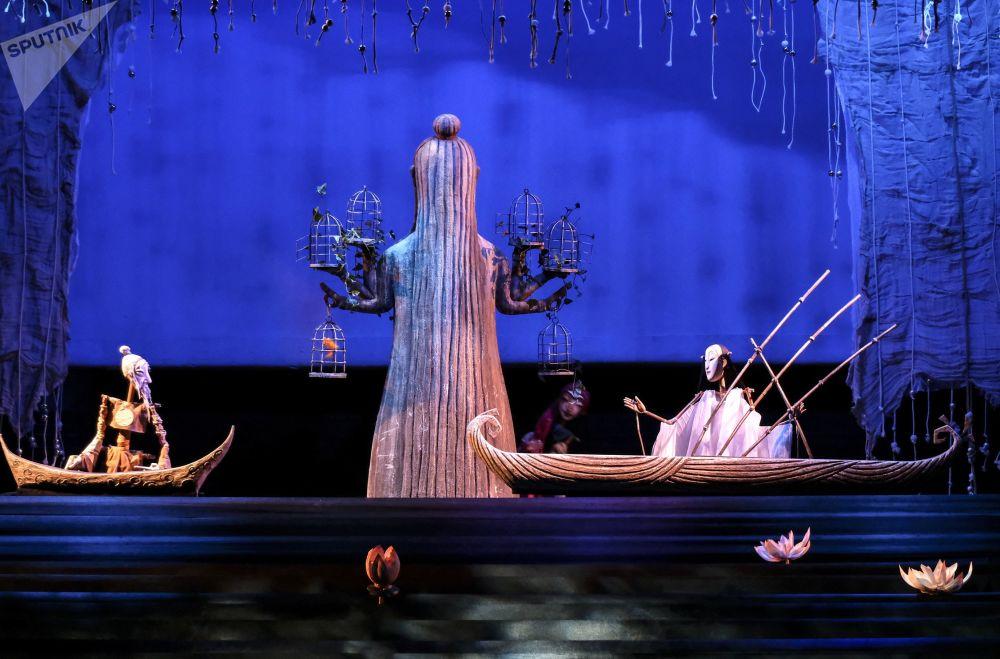 """在上层木偶剧院(手套,手杖和其他构件)中,一个或多个木偶戏演员位于屏幕后面(好像在管弦乐队的坑中)。    照片:表演""""图兰朵""""的演员们。"""
