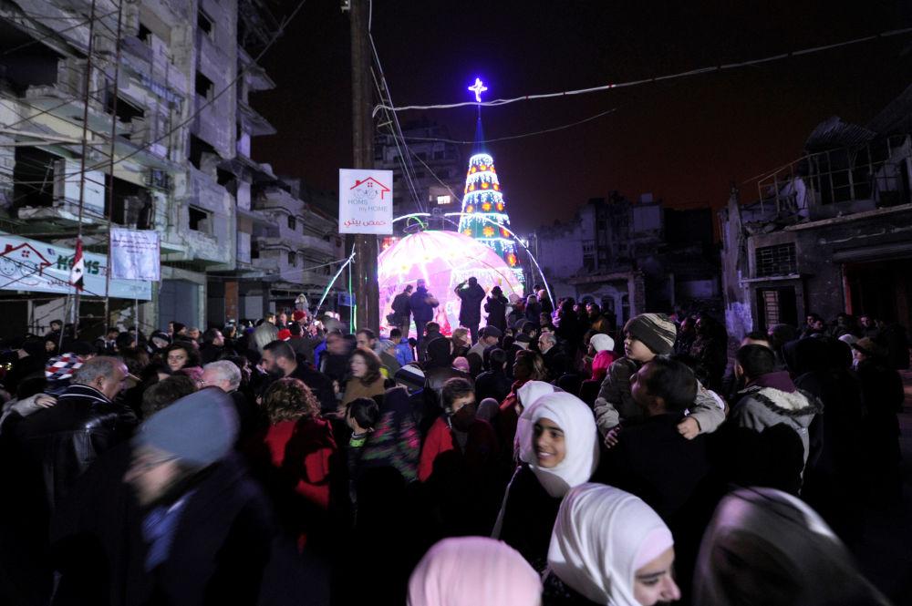敘利亞霍姆斯市聖誕樹旁的人們。