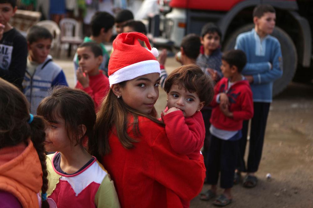 貝魯特發放禮物時帶著一名敘利亞孩子的黎巴嫩女孩。