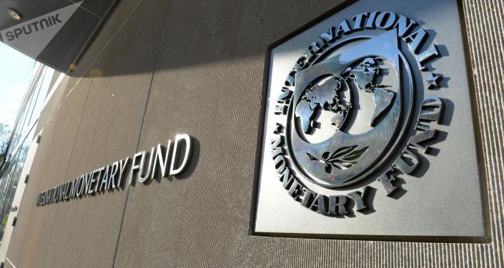 Табличка с国际货币基金组织下调中美经济增长预测 логотипом Международного валютного фонда на стене здания МВФ
